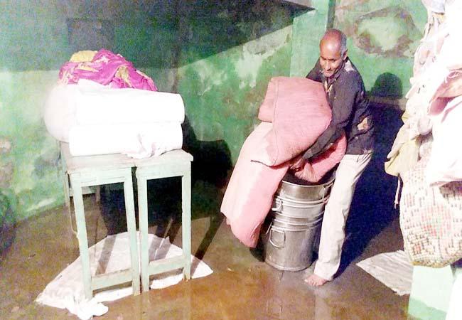 मोहता चौक स्थित दुकान के तलघर में भरे पानी से खराब हुए सामान को बाहर निकालते। फोटो : राहुल व्यास