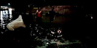 बीकानेर में सूरसागर तालाब के आगे नाले में गिरे बाइक सवार को निकालते लोग।